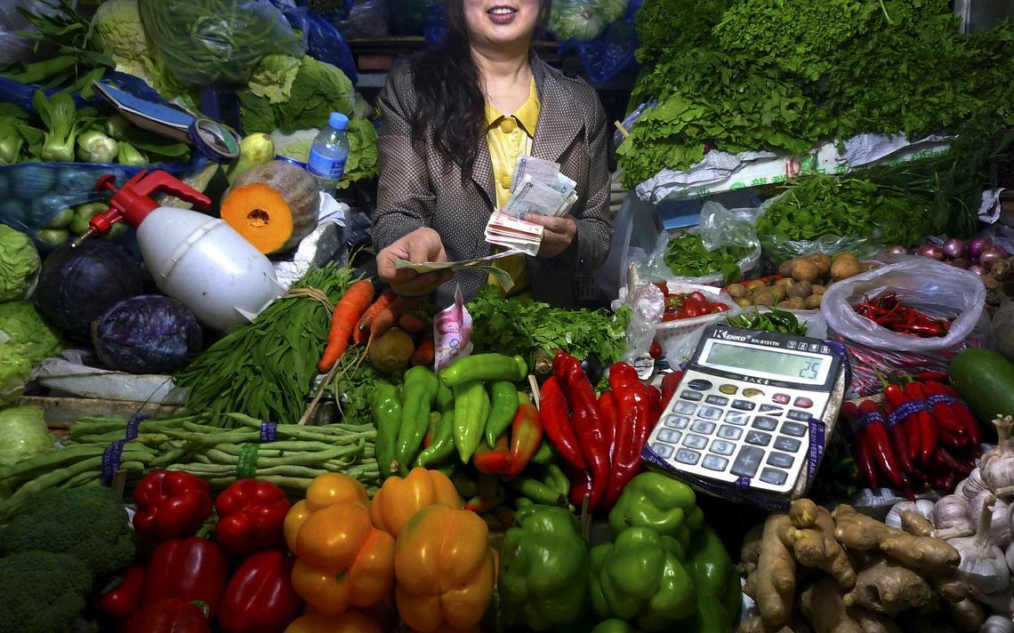 Vendedora de vegetais segura notas de dinheiro em Pequim, na China, em 2011