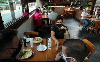 Três homens de máscara compartilham uma mesa, em que há pratos com arroz, carne e batata frita. Ao fundo, há outras meses com clientes, mas a uma distância maior do que o comum