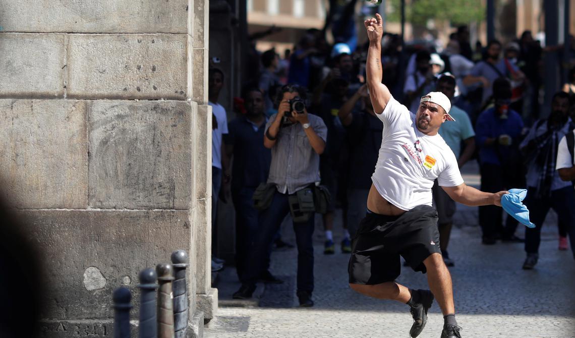 Manifestante atira garrafa contra a polícia durante votação que revogou prisão de deputados no Rio