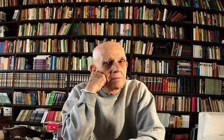 O escritor Rubem Fonseca com a mão no queixo, encarando a câmera, em frente a uma enorme estante de livros.