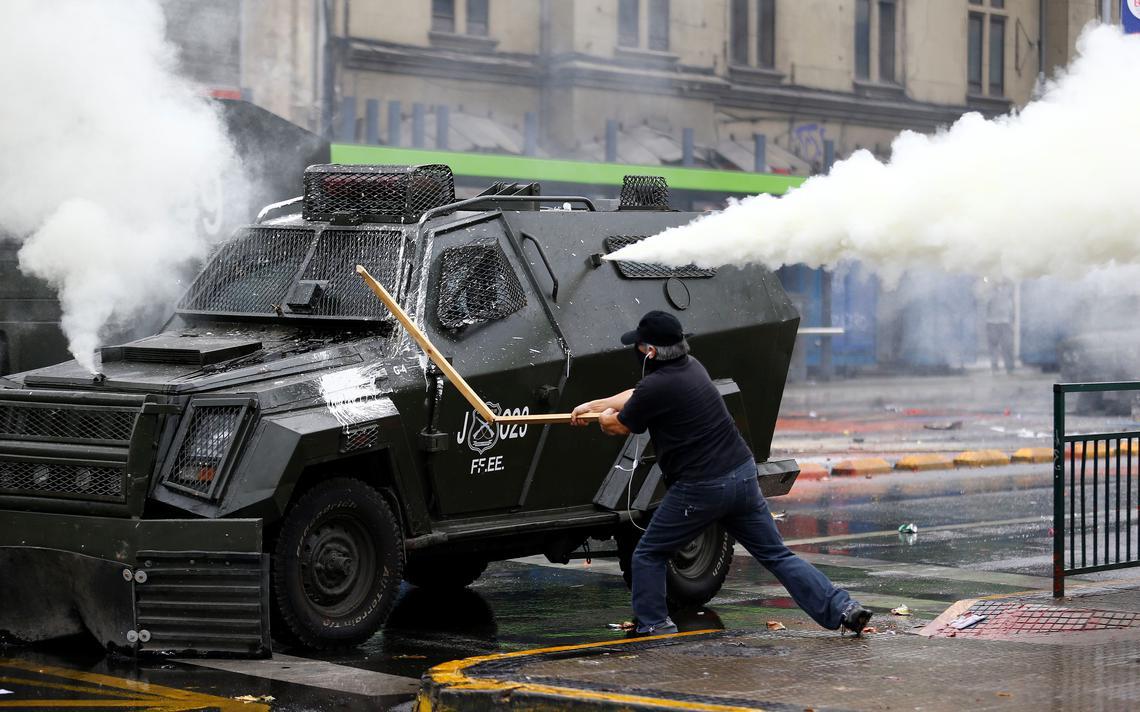 Manifestante em Santiago ataca carro blindado da polícia