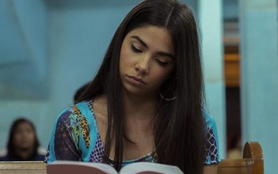 Uma jovem de cabelo liso e escuro está sentada em um banco de igreja lendo o que parece ser a bíblia