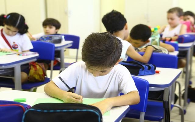 Crianças fazem lição sentadas, em fileiras, em uma sala de aula.. Elas olham para seus papéis na escrivaninha. Suas escrivaninhas são brancas, e as cadeiras, azuis. Seus uniformes também são brancos.