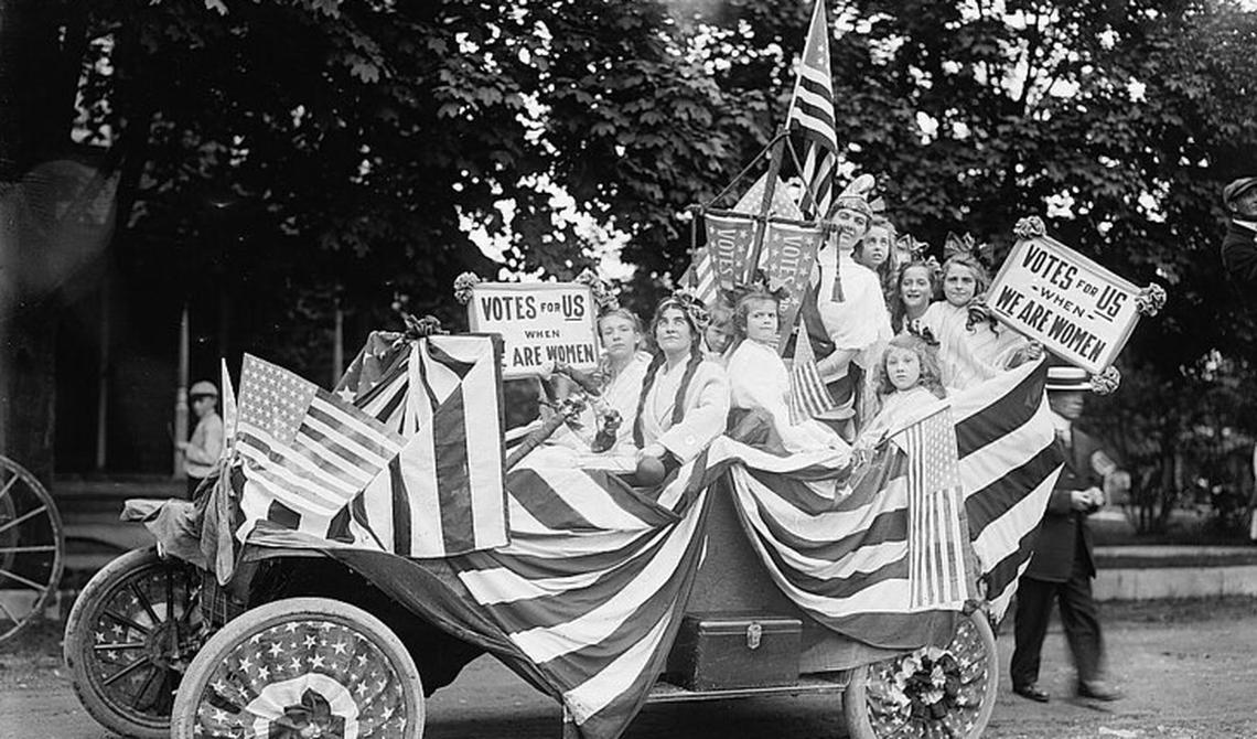 Imagem em preto-e-branco mostra mulheres e crianças sentadas em carro aberto, com bandeiras e cartazes pedindo direito ao voto.