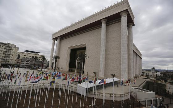 Foto do Templo de Salomão, mostra uma construção enorme e imponente, com colunas altas, coqueiros e bandeiras na frente