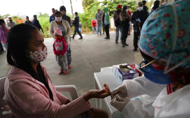 Agente de saúde coleta sangue do dedo de mulher para teste de covid. As duas usam máscaras e estão sentadas uma na frente da outra, enquanto moradores de quilombo formam filas ao fundo