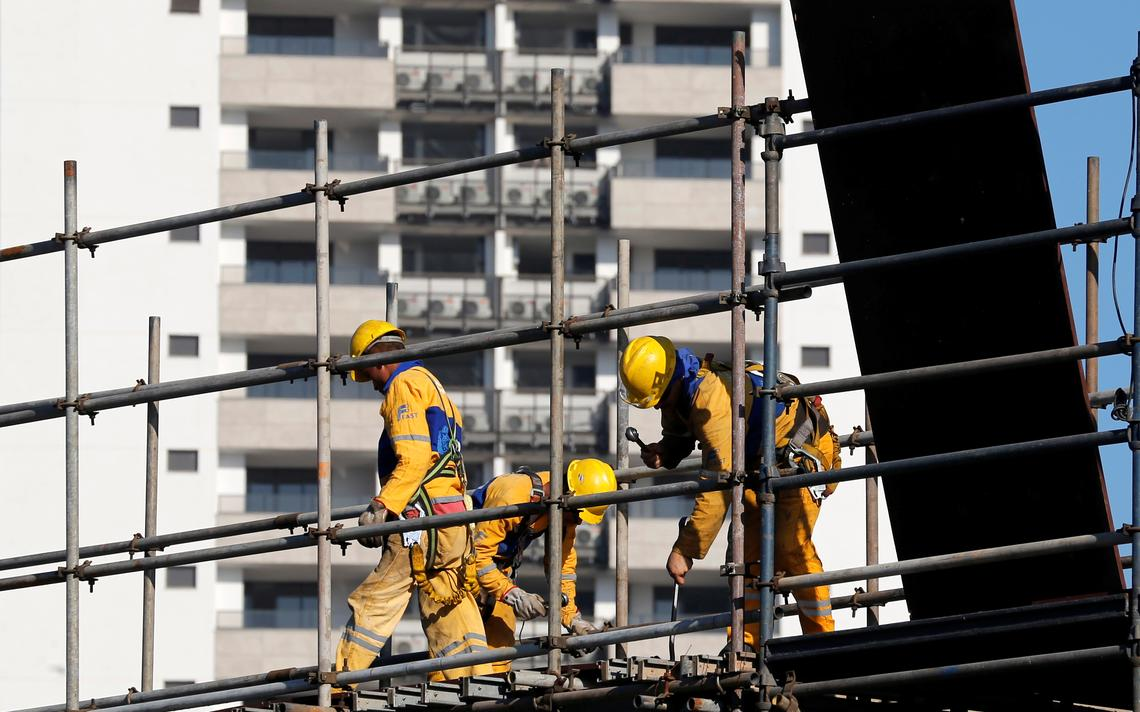 Homens trabalham na construção da Vila Olímpica, no Rio