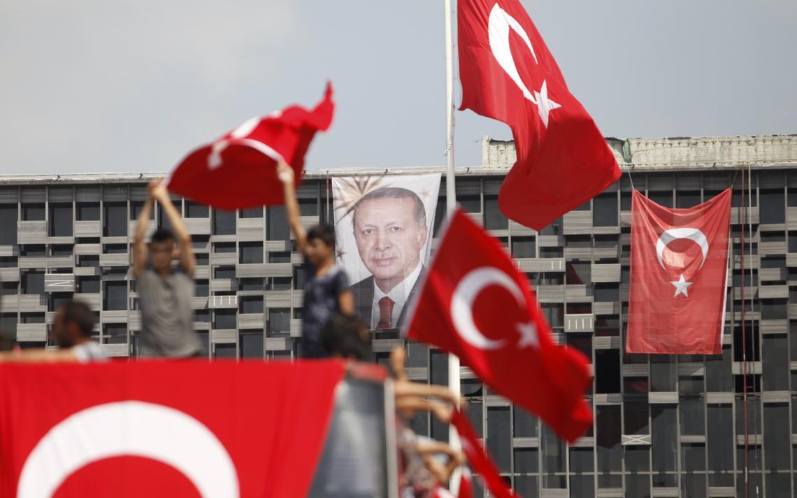Apoiadores do presidente da Turquia balançam bandeiras após golpe dar errado