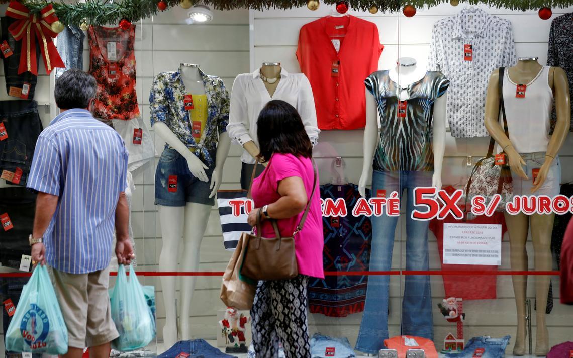 Consumidores olham vitrine de loja em São Paulo