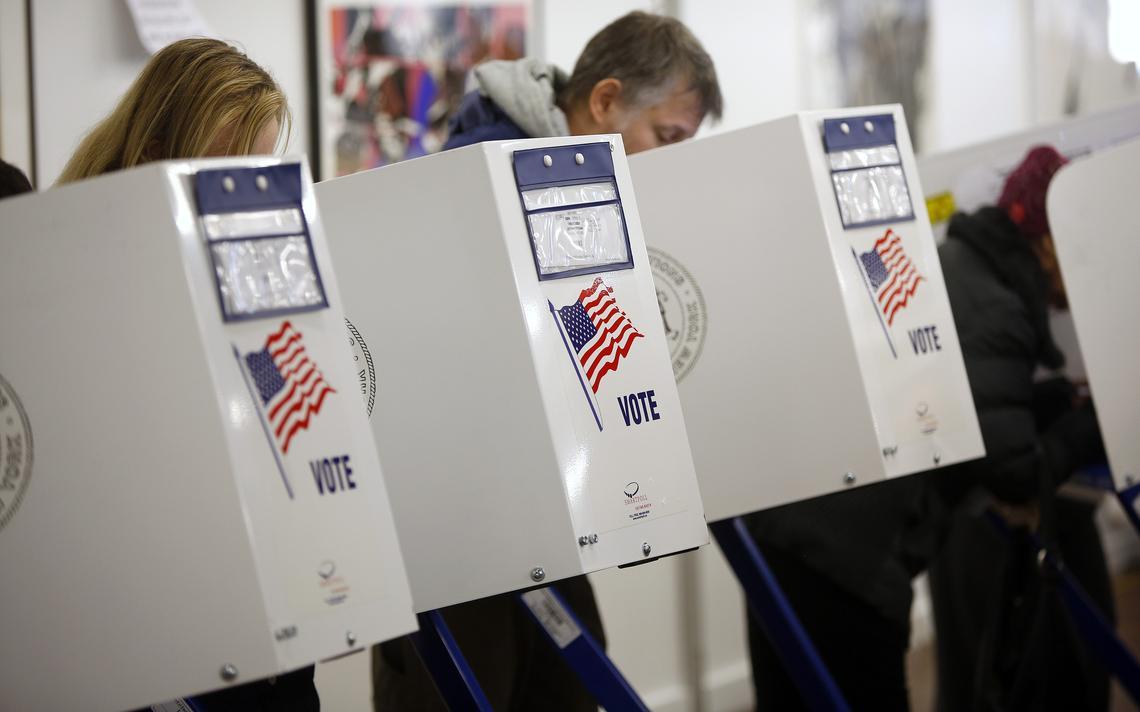 Eleitores em cabines de votação nos Estados Unidos