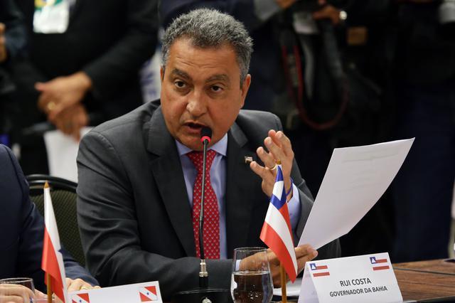 Sentado, Rui Costa fala ao microfone e gesticula. Com a mão direita, ele segura um papel. À frente dele na mesa, uma pequena bandeira do estado da Bahia.
