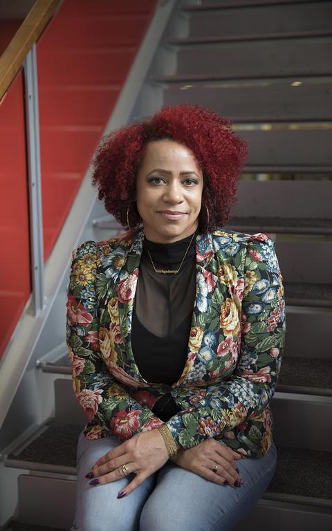 Mulher negra, com cabelo pintado de vermelho e blazer florido, olha para a câmera sentada nos degraus de uma escada e com os braços cruzados e as mãos pousadas sobre o colo