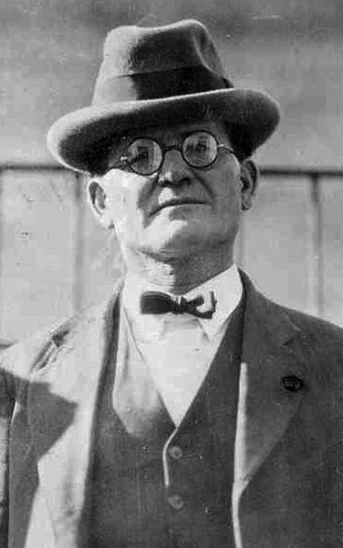 The man in the hat, the glasses, the suit and bow tie looking to camera