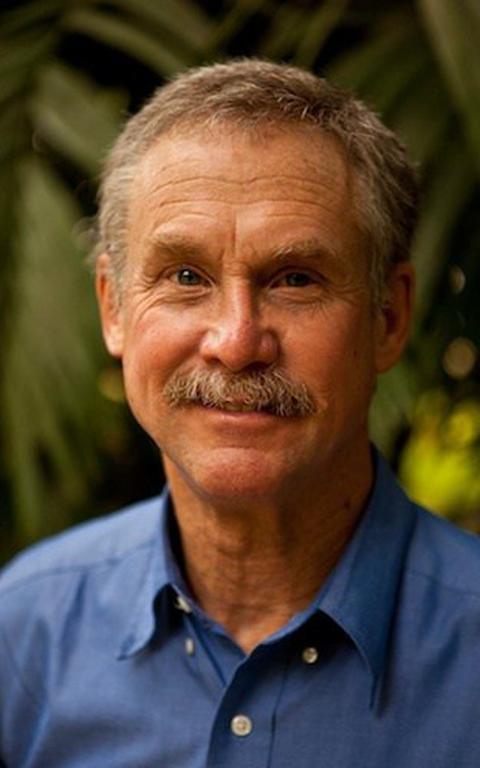 Um retrato de David Quammen, um homem branco de cabelos brancos e olhos azuis, vestindo uma camisa também azul.