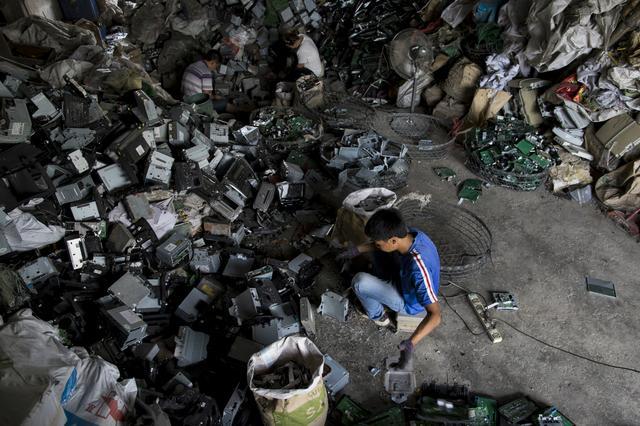 Jovem busca itens aproveitáveis de pilha de lixo eletrônico na cidade de Guiyu, em 2015