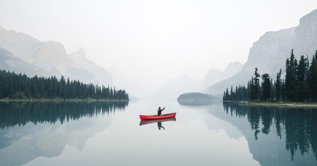 Pessoa rema em canoa em meio a montanhas